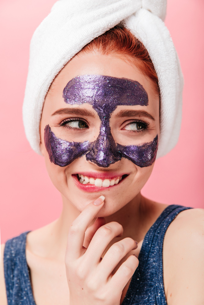 spectacular-young-woman-doing-spa-treatment-with-sincere-smile-studio-shot-glad-girl-with-face-mask-towel